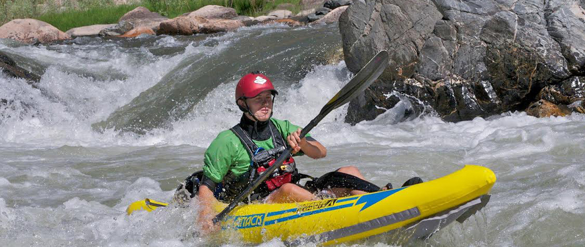 Amabassador Liz paddling whitewater in the Attack Kayak